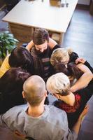 kreativa affärsmän som bildar kram på kontoret foto