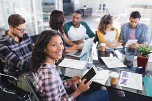 porträtt av affärskvinna som sitter med teamet medan du arbetar på kontoret foto