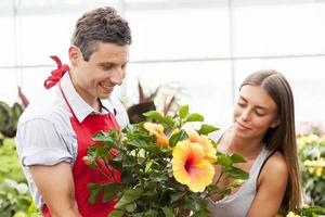 leende säljare säljer en anläggning till en vacker kund foto