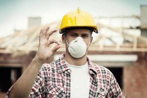 manuell arbetare med hård hatt och skyddande mask foto