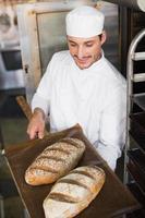glad bagare innehav bricka med färskt bröd foto