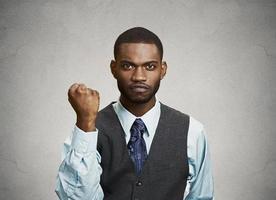 arga vilda upprörda förbannade ung man, arbetare som arbetar företagare att sätta upp näven foto