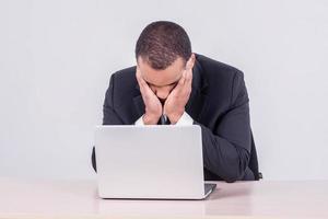 trött affärsman. le afrikansk affärsman som sitter vid ett skrivbord foto