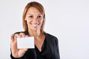 leende latina affärskvinna som håller upp tomt kort foto