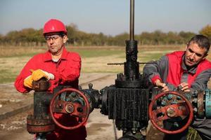 två skickliga olje- och gasingenjörer i aktion vid oljebrunnen foto