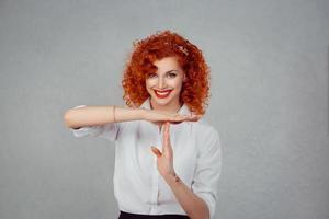 Paus. närbild porträtt, ung, glad, leende kvinna visar time-out gest med händerna isolerad på grå vägg bakgrund. positiva mänskliga känslor ansiktsuttryck, känsla kroppsspråk reaktion foto