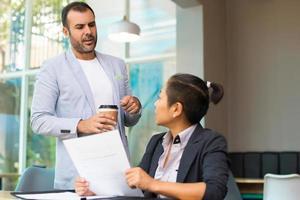 fundersam latinamerikansk affärsman med kaffekopp som pratar med chefen