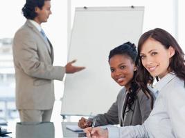 två unga leende anställda som arbetar medan de lyssnar på en presentation foto