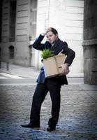 frustrerad affärsman på gatueldad bärande kartong foto