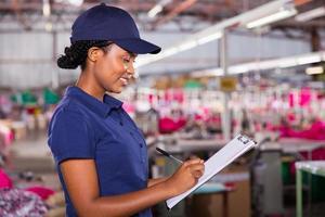 textil kvalitetskontrollant skriver på Urklipp foto