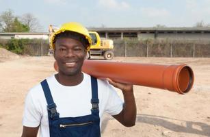 skrattar afrikansk arbetare med pipa foto