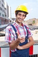 glad byggnadsarbetare med svart hår foto