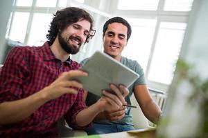 grafiska formgivare som använder den digitala surfplattan vid skrivbordet foto