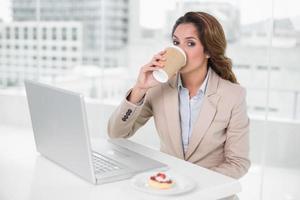 affärskvinna som dricker kaffe vid sitt skrivbord framför bärbar dator foto