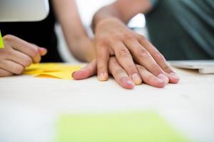 närbild av kontorskollegor med handen på skrivbordet foto