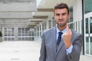 humörig affärsman som visar långfingret foto