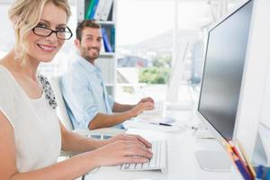 avslappnade unga par som arbetar på datorn på kontoret foto