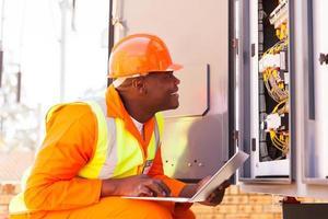 afrikansk elektriker som kontrollerar datoriserad maskinstatus foto