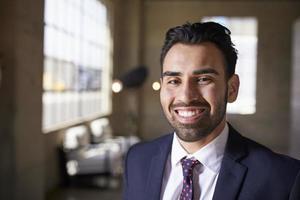 ung latinamerikansk affärsman som ler mot kameran, närbild foto