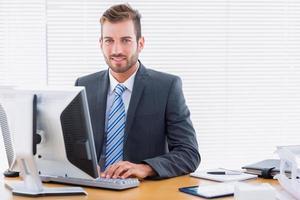 ung affärsman som använder datorn på kontorsskrivbordet foto