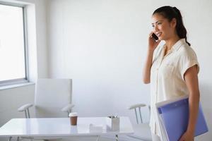 avslappnad affärskvinna i telefoninnehavsmappen foto