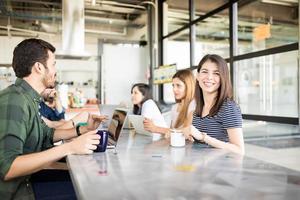 kvinna med kollegor på cafeterian foto