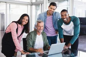 porträtt av mogen affärsman och leende kollegor vid skrivbordet foto
