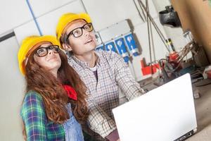 ett par tekniker konsulterar datorn i ett stålverk foto