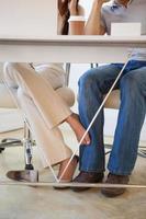 avslappnad affärskvinna som spelar fotboll med kollega under skrivbordet foto