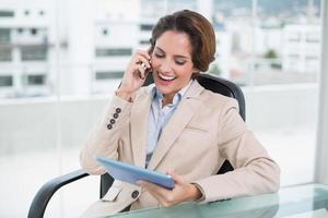 brunett skrattande affärskvinna med smartphone och håller surfplatta foto