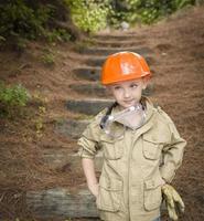 bedårande barnpojke med stora handskar som spelar hantverkare utanför foto