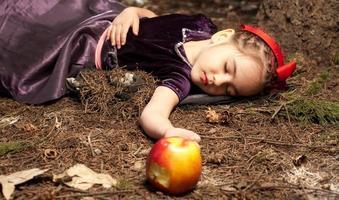 snövit liten flicka med förgiftat äpple foto