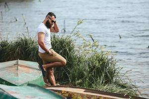 amerikansk skäggig man som använder telefonen nära floden foto