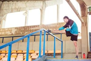 idrottsman gör värmande stretchingövning på stadion