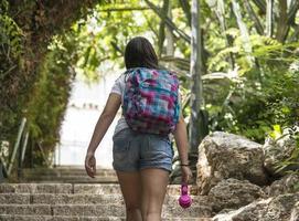 tonårsskolflicka med en ryggsäck och hörlurar foto