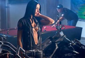 kvinna nära motorcyklar, man spelar biljard foto