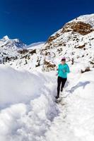 glad kvinna längdskidåkning på vintern foto