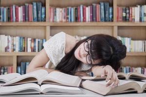 student sover och drömmer i biblioteket foto