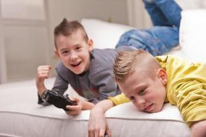 två barn som spelar videospel foto