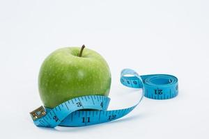 lagerbild av det gröna äpplet och måttbandet foto