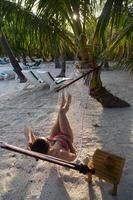 kvinna på stranden i en hängmatta foto