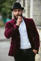 rik man med ett skägg röker elektronisk cigarett foto