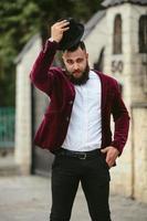 rik man i en jacka nära sitt hus foto