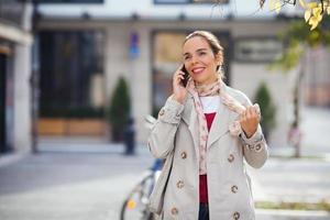 kvinna på gatan som pratar i telefon foto
