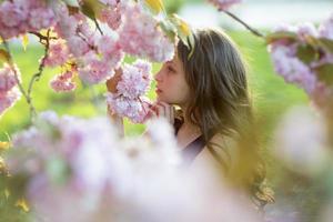 söt flicka mitt i körsbärsblomning foto