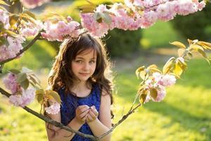 liten flicka som håller körsbärsblom foto