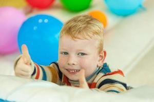 liten pojke som ligger på golvet omgiven av färgglada ballonger foto