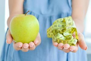 kvinna håller äpple och måttband föreslår diet koncept foto