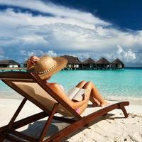 ung kvinna som läser en bok på stranden foto