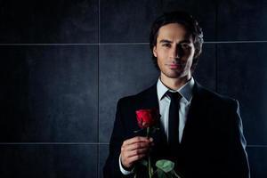 porträtt av den stiliga romantiska unga mannen i formalwear holding rose foto